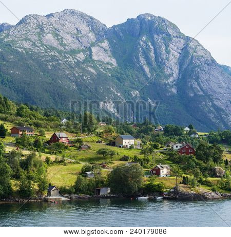 View of Jondal Commune and Hardangerfjord Fjord, Norway. Summer landscape with a Scandinavian village. Sunny weather