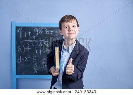Cheerful Smiling Schoolboy In Uniform With Book.  He Is Happy To Start Learning And Holding Thumb Up