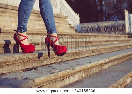 Woman Wearing Blue Jeans And Red High Heel Shoes In Old Town. The Women Wear High Heels Walk Down St