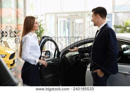 Young Woman Choosing New Car With Salesman In Salon
