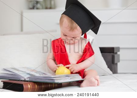 Portrait Of Baby Boy In Graduation Cap Holding Apple And Reading Book. Concept Of Early Child Educat