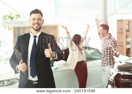 Salesman With Clipboard And Happy Couple In Salon. Buying New Car