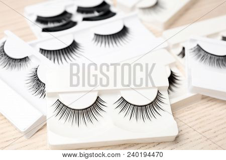 Different Types Of False Eyelashes In Packs On Wooden Background