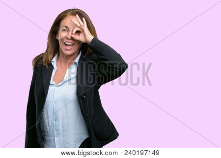 Middle age business woman looking at camera through her fingers in ok gesture. Imitating binoculars, beautiful eyes and smile