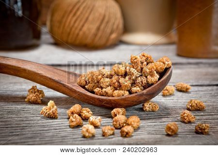 Dried Mulberries In A Wooden Spoon In Kitchen