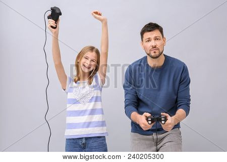 Happy teenage girl and her upset father with video game controllers on grey background