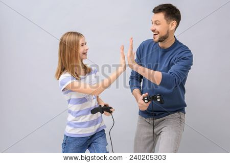 Happy teenage girl and her father with video game controllers on grey background