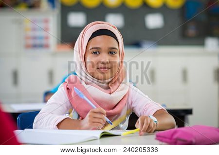 Happy young smiling girl wearing hijab and looking at camera while sitting at desk with exercise book Elementary muslim schoolgirl writing notes in classroom. Portrait of arab school girl in chador.