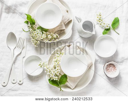Served empty table with white crockery, flowers, napkins on white background, top view. Cozy home serving food table concept poster