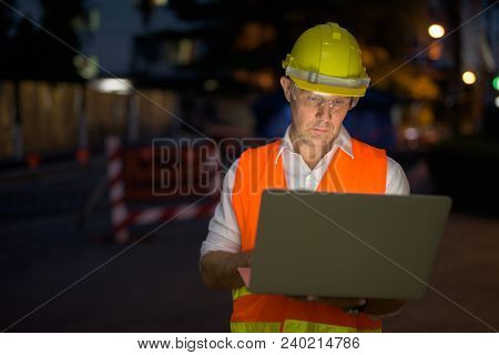 Portrait Of Mature Man Construction Worker At The Construction Site In The City At Night