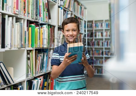 Happy smiling boy reading a book in the library at school. Portrait of cute child in a bookstore looking at camera. Confident pupil borrow a textbook from the library.