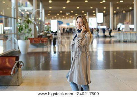 Woman Talking By Mobile Phone In Airport Waiting Room. Concept Of Advantageous Tariff Plan For Trave