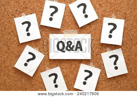 Q&a Or Questions And Answers On A Piece Of White Paper And Many Question Marks On Brown Cork Board.