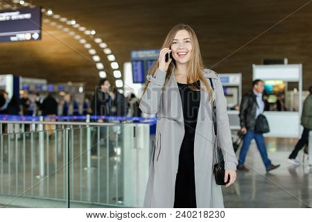 Beautiful Businesswoman Talking By Smartphone At Airport Hall, Wearing Grey Coat And Bag. Concept Of