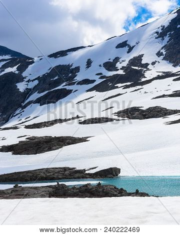 Snow, Ice, Glacier Water And Mountain Top In Summer In Norway