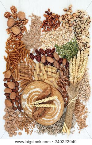High fibre health food concept with fresh wholegrain rye bread, whole wheat pasta, nuts, cereals and grains, super foods high in omega 3, antioxidants and vitamins.