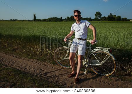 Handsome Man Posing With His Retro Italian Bicycle On Green Field