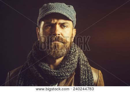 Serious Bearded Man With Long Beard Dressed In Brown Leather Jacket, Gray Cap And Scarf. Young Beard