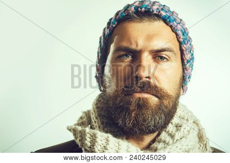 Fashion For Men. Serious Bearded Man With Long Beard Dressed In Knitted Colored Hat And White Scarf.