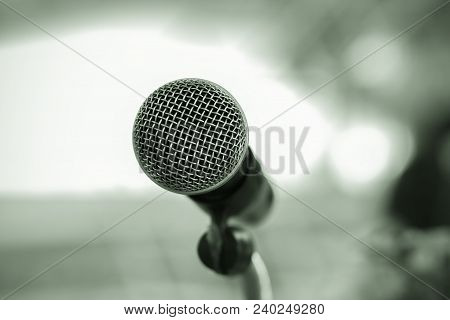 Microphone On Abstract Blurred Of Speech In Seminar Room Or Speaking Conference Hall Light, Event Ba