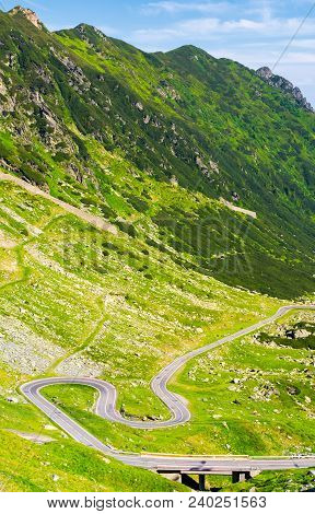 Legendary Transfagarasan Road In Romanian Mountains. Winding Serpentine Among The Grassy Hills On A