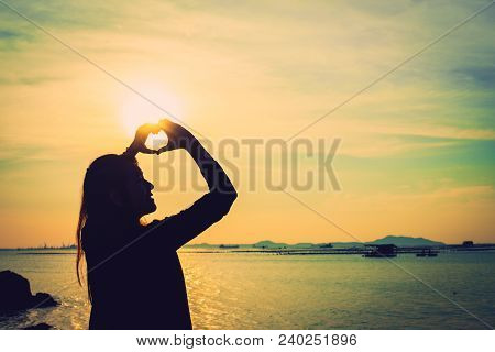 Silhouette Of Heart Shape Being Made By Young Woman Hands With Sunlight On Beach. Sunset At The Sea.