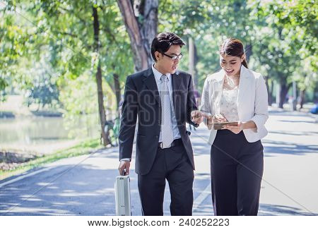 Businessman And Businesswoman Talking Outdoors About Their Business With Tablet And Walking Through