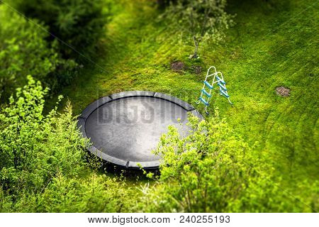Large Trampoline In A Garden With A Ladder Surrounded By Green Trees Seen From Above