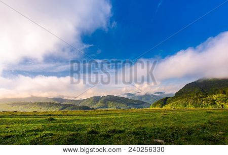 Beautiful Sunrise In Mountains. Gorgeous Cloudscape Above The Ridge In The Distance. Clear Grassy Me