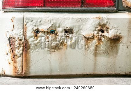 Damaged Car. White Car With Rusty And Corroded Metal Peeled Paint And Holes Close Up