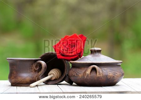 Tea Leaves In A Tea Cup Made Of Clay With A Red Rose