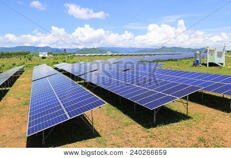 On Ground Solar Farm Under Blue And Cloudy Sky Mountain Background