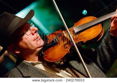 Musician In Hat Playing On Violin In The Night