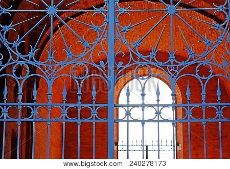 Vintage, metal gates with openwork wrought-iron grilles. Arch brickwork. poster