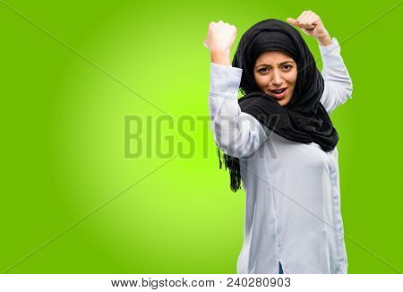 Young arab woman wearing hijab showing biceps expressing strength and gym concept, healthy life its good