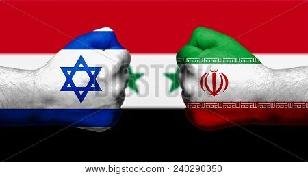 Flags Of Israel And Iran Painted On Two Clenched Fists Facing Each Other With Flag Of Syria In The B