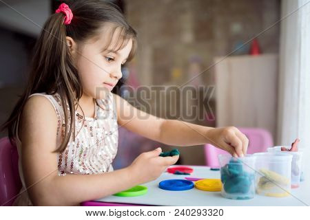 Child Girl Is Playing With Putty At Home