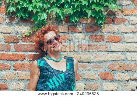 Beautiful Retro Older Woman In Front Of The Brick Wall