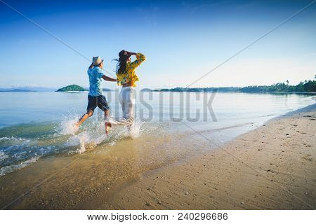 Happy Middle Aged Couple Running On A Beach, Koh Mak Thailand