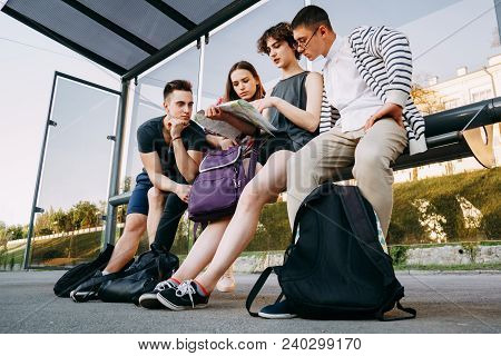 Traveling, Sightseeing, Group Travel, City Tour, Togetherness. Tourists Sitting At Bus Stop Planning