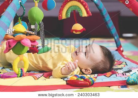 Sweet Baby Playing With Toys On Carpet