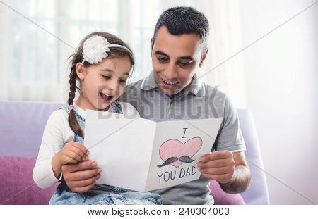 Happy Father's Day Portrait. Child Daughter And Her Daddy Are Hugging And Reading The Surprise Postc