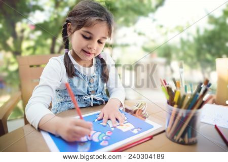 Little Girl Is Painting Picture Outdoors In Summer