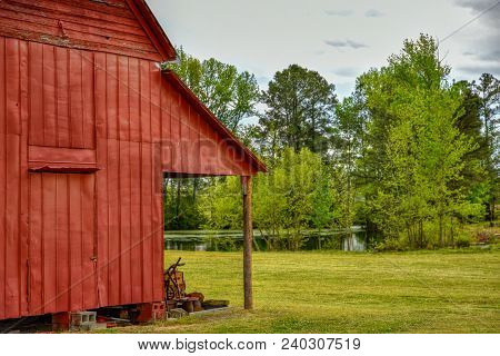 A closeup of the side of an old red barn with a lush green pond in the background.