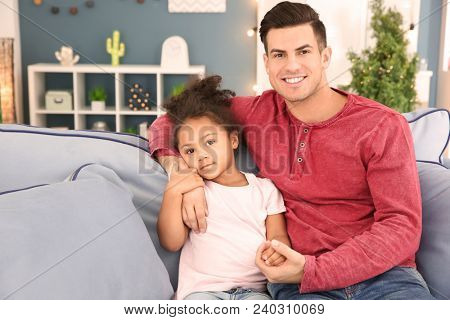 Young man and little African-American girl indoors. Child adoption