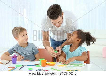Young man and little kids playing together indoors. Child adoption