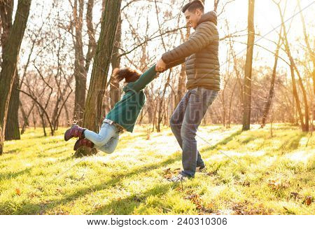 Young man playing with little girl outdoors on sunny day. Child adoption