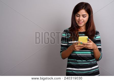 Studio Shot Of Young Beautiful Indian Woman Using Mobile Phone Against Gray Background