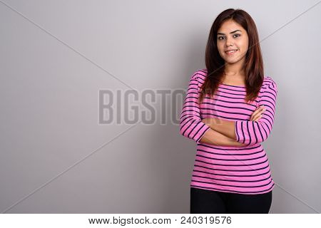 Studio Shot Of Young Beautiful Indian Woman Against Gray Background