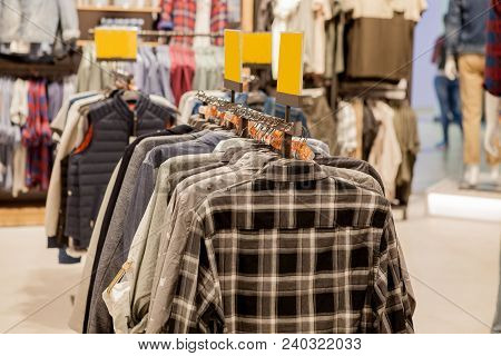 Clothes Hang On A Shelf . Cloth Hangers With Shirts. Men's Stylish Clothes. Fashion And Trade Concep